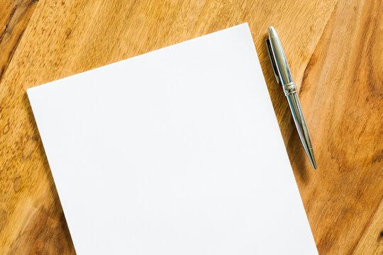 Blatt Papier auf Holztisch mit Stift