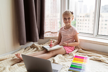 Little child learn english online at home. Homeschooling and distance education for kids. Caucasian Girl student drawing english letters at the notebook during coronavirus covid-19 quarantine