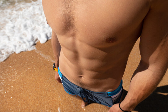 Close-up of an athletic physique the body of a young man pectoral muscles press and arms. Top view of a man on the beach