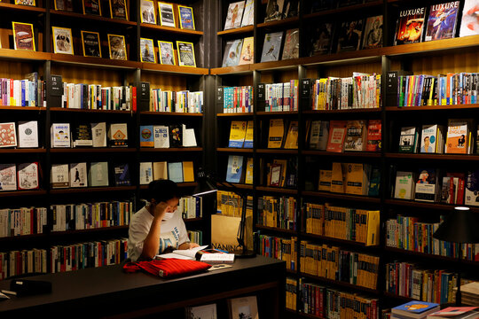 A woman wearing a mask reads a book amid the coronavirus disease (COVID-19) pandemic at a book store in a giant mall in Seoul