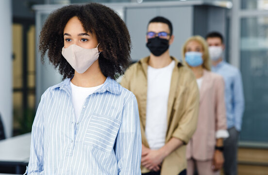 New normal and temperature check before work. Millennial multiracial employees in protective masks stand in line with social distancing at office in morning