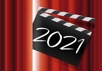 Un clap de cinéma avec l'inscription 2021, passe au travers du rideau rouge d'une scène de spectacle, pour présenter la nouvelle année.