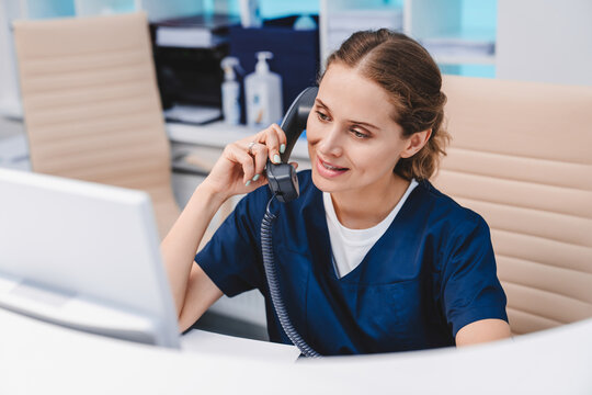 Young female receptionist talking on phone in clinic while sitting and looking on pc monitor