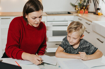 Tutoring. Home schooling. Teacher and pupil. A woman and a blonde boy at the table.