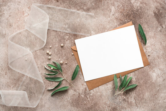 Feminine wedding invitation. Blank paper card mockup, brown envelope, ribbon, and olive branch with leaves. Modern stationery scene. Beige grunge background. Top view, flat lay.