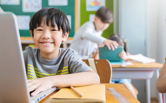 Portrait of Asian little boy using computer to learn lessons in elementary school. Student boy studying in primary. Children with gadgets. Education knowledge, technology internet network concept