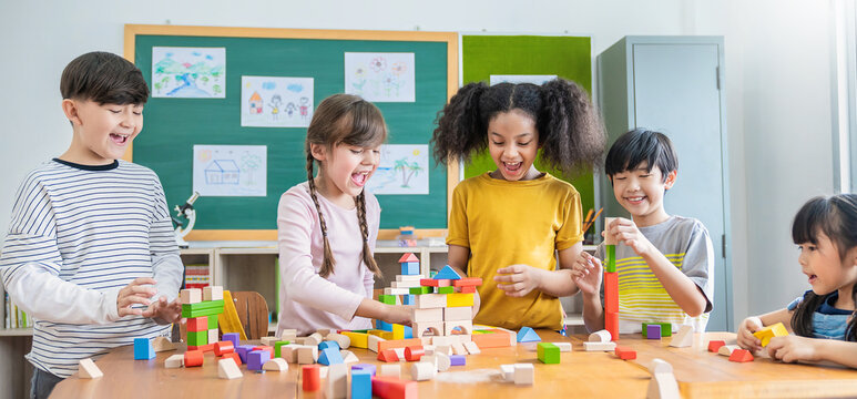 Portrait of asian caucasian little children playing colorful blocks. Learning by playing education group study concept. International pupils doing activities brain training in primary school.