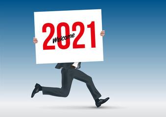 Pour présenter la future stratégie d'une entreprise, un homme d'affaire cours en portant une pancarte blanche sur laquelle est écrit bienvenue à l'année 2021.