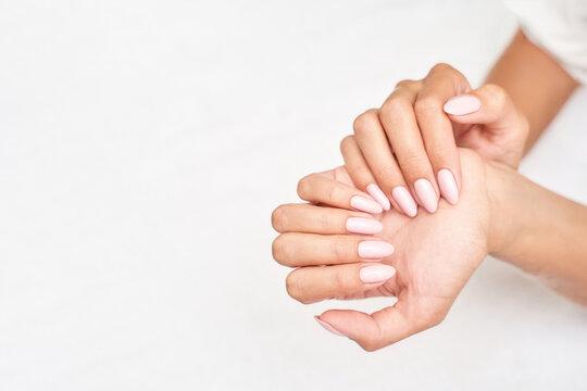 Classic pink wedding nail manicure on white backdrop. Spa treatment concept. Towel background. Natural hygiene. Health care. Beauty spa salon. Salon procedure Woman body care.