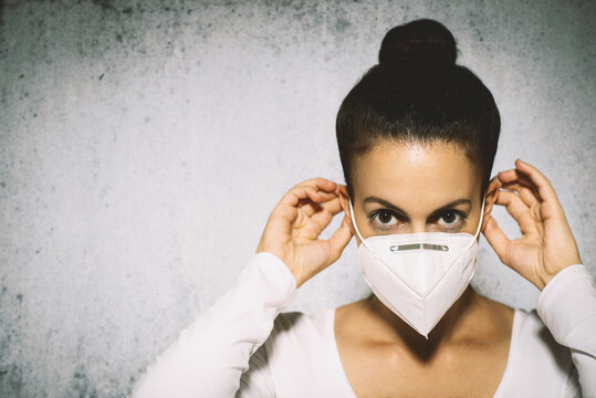 Woman demonstrating how to put on surgical mask