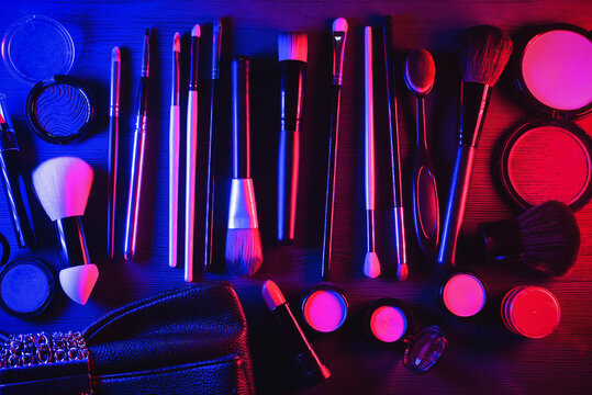 Makeup accessories concept background. Make up brushes and clutch bag on the table.