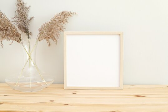 Square wooden frame mockup for photo, print, painting, artwork presentation, boho style decorations, wooden shelf.