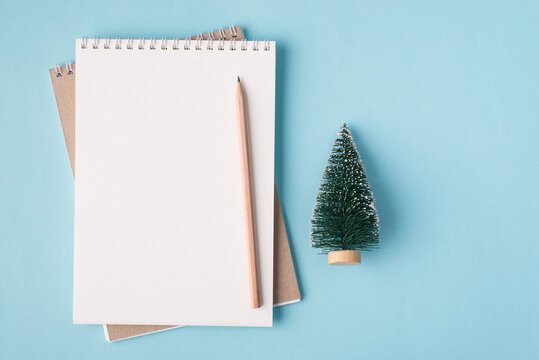 Christmas holiday concept. Top above overhead view flat lay photo of a blank notebook and a small christmas tree isolated on pastel blue color background with copyspace