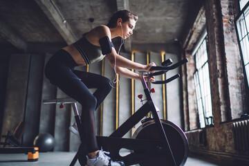 Determined sportswoman training on cycling machine
