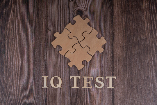 IQ test, text and puzzle on a wooden background. Creative idea, mind, thoughts, level of intelligence