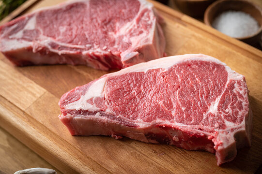 raw steak meat on cutting board in bright kitchen