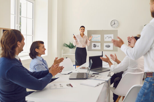 Happy employees celebrating sales increase in corporate meeting with sales manager
