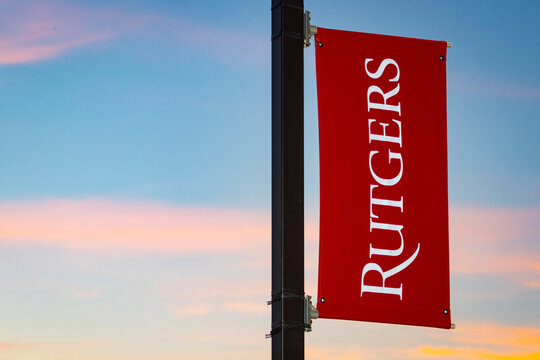 Rutgers University logo on banner against colorful skies