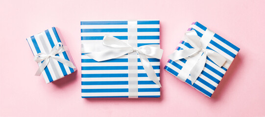 Wall Mural - wrapped Christmas or other holiday handmade present in paper with White ribbon on pink background. Present box, decoration of gift on colored table, top view