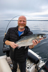 Man holds fresh caught wild Coho Salmon fish