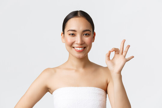 Beauty, cosmetology and spa salon concept. Close-up of beautiful asian female in towel showing okay gesture, satisfied with excellent service in beauty clinic, pleased with results, smiling delighted
