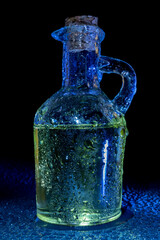 Edible oil bottle covered with water droplets. A bottle of oil and water drops.