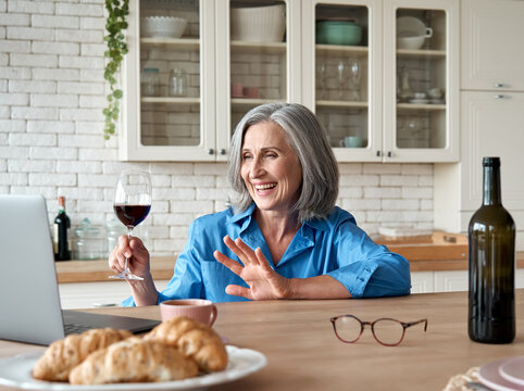 Happy 60s mature woman drinking wine video calling friend on laptop at home. Smiling old middle aged lady holding glass waving hand talking by online social distance chat meeting sit at kitchen table.