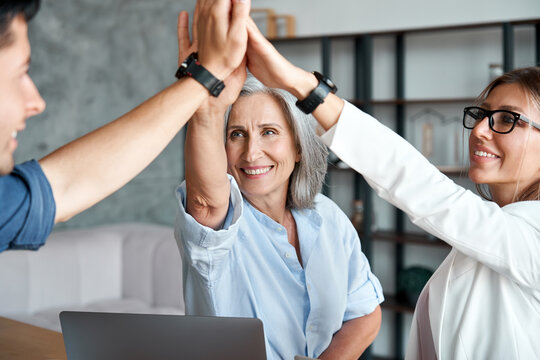 Happy mature old female mentor teacher executive giving high five to young enthusiastic employees, interns, students united team as teamwork support, professional leadership and partnership concept.
