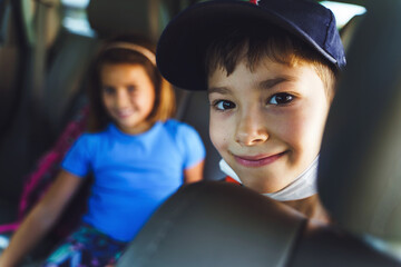 Close up portrait of small caucasian boy sitting on the back seat of the car in summer day - Brother and sister little children traveling - selective focus