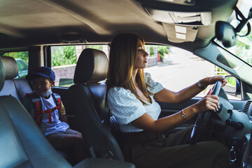 Side view on caucasian woman driving her little son in car - Mother taking small boy first grade pupil to school - Morning daily routine motherhood concept