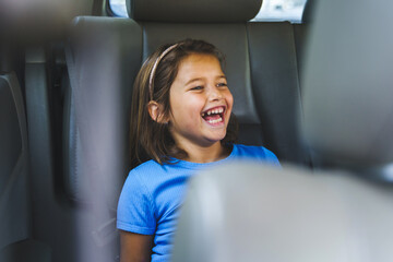 Close up portrait of small girl sitting on back seat of the car smiling in summer day