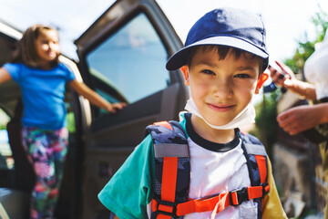 Small caucasian boy first grade pupil with backpack on shoulders exit the car in sunny day or morning - brother and sister Back to school daily routine education concept - selective focus