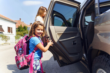 Little girl in sunny day or morning going to school - small pupil first grader with backpack on shoulders and her mother entering the car - Real people education concept
