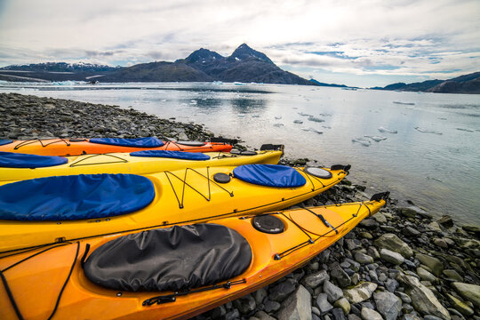 Double kayaks parked on the bay on scenic mountain ocean bay during arctic expedition