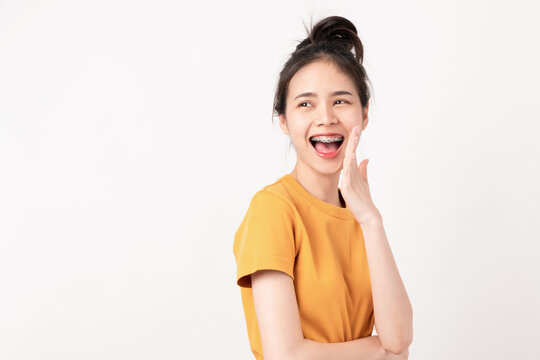 Cheerful Asian woman standing and announcing with hands to the mouth and telling a secret in wearing a yellow shirt, Looking to the side.