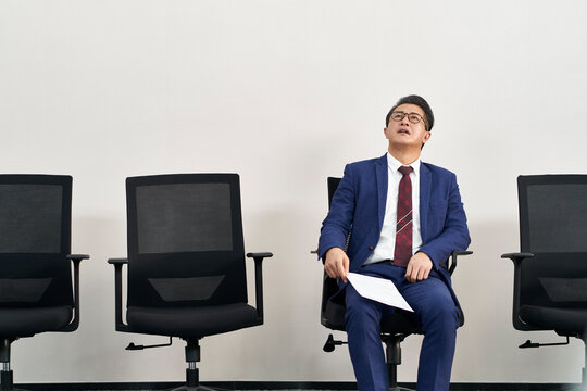 older asian male job seeker anxiously waiting for interview