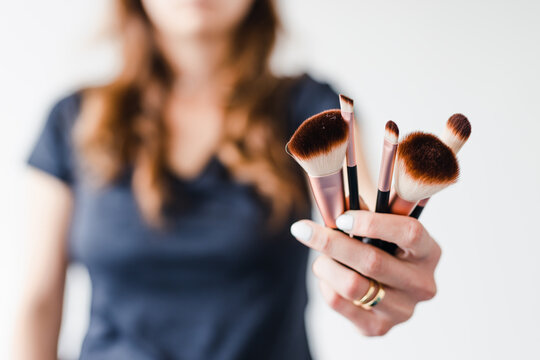 girl holding make-up brushes in front of the camera showing the product, beauty bloggers and influencers reviews or tutorials
