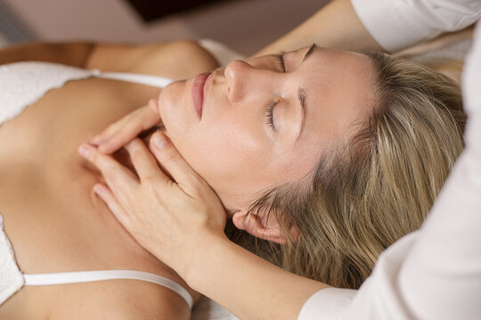 Young woman enjoying facial at spa salon. A beautiful caucasian client 35 years old receiving skin care treatment procedure in clinic. Massage therapy, anti aging.