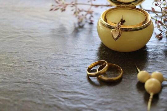 Gold Jewellery. Bracelet, wedding rings, earrings, gold chain, heart pendant, alabaster box in a dark background.