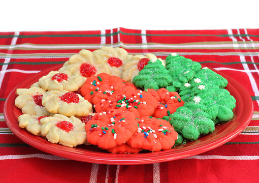 Sugar cookies decorated for Christmas on a red plate.