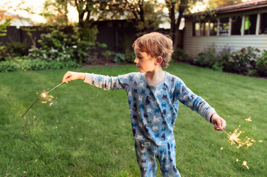 Small boy enjoying sparklers in the garden in the evening