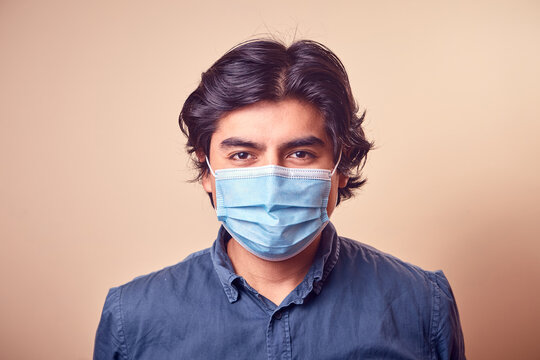 Un hombre joven sonrisa mientras usa mascarilla quirúrgica en el rostro y guantes.