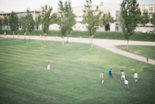 defocused photograph of a group of friends playing football in the park.