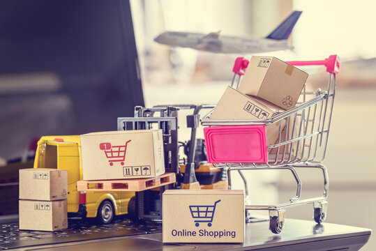 Online shopping, logistics, supply chain and shipment service, e-commerce concept : Boxes of goods, trolley, air plane, delivery van on a laptop, depicts customers uses internet to order / buy things