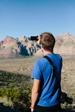 Man with camera taking picture of mountains in the desert
