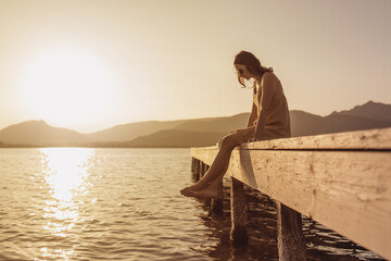 Pensive single Caucasian pretty young woman sitting on a pier of a lake looking down to the water at sunset - Vintage orange color mood