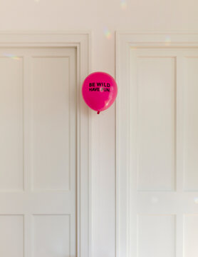 Magenta balloon with black words saying Be wild, have fun