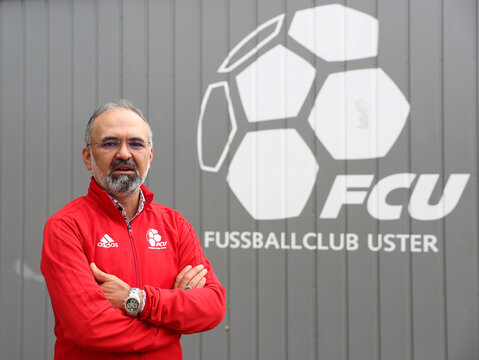 Ali Oezcan, vice-president of Swiss soccer club FC Uster poses in front of club logo in Uster