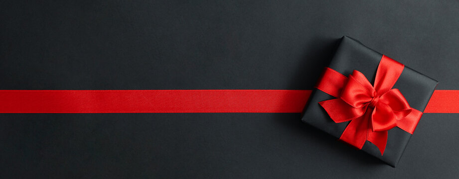 Gift box and red ribbon on black background