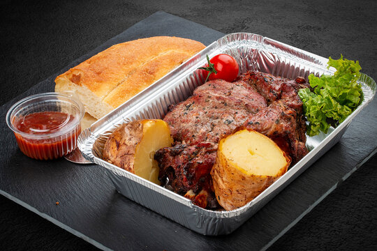 Grilled pork steak with baked potatoes, matnakash and red sauce. Food delivery. Served on aluminium lunch box.